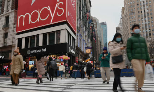 People wear facemasks as they walk near Macy's flagship store in New York City.